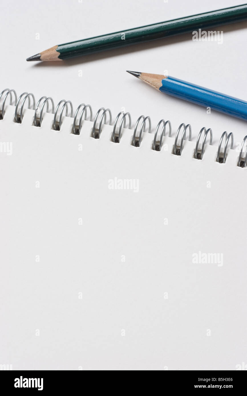 close up photograph of a clean white sketch pad and artists pencils Stock Photo