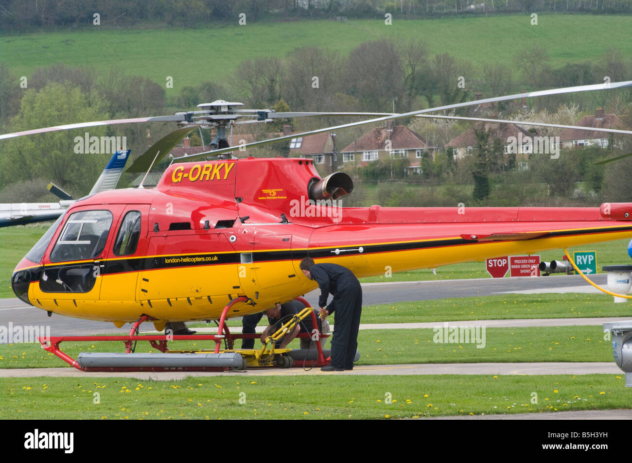 Mechanics Repairing Working On A Red and Yellow Helicopter G ORKY Redhill Aerodrome Surrey UK Helicopters - Stock Image