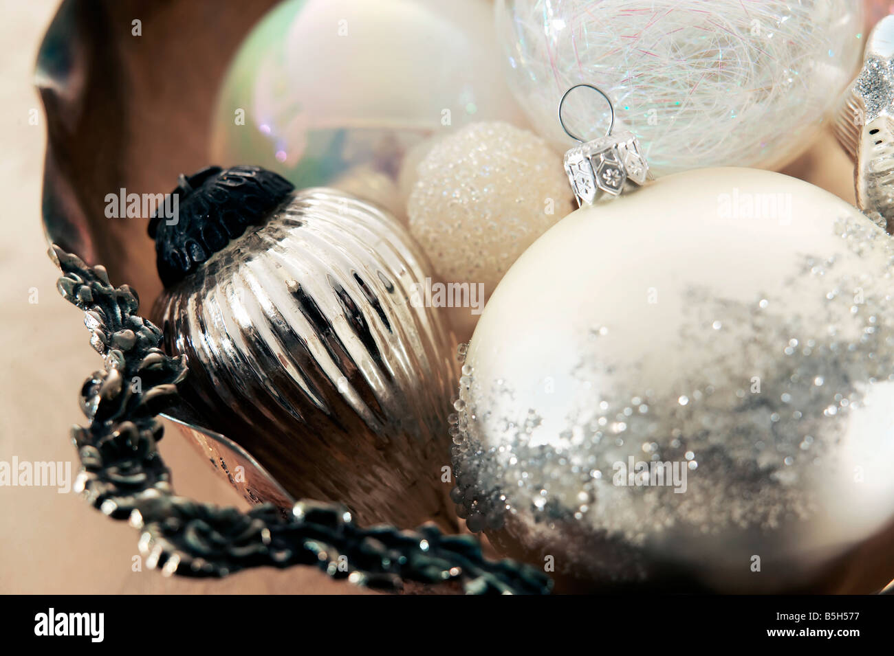 white and silver christmas ornaments gathered in a antique silver bowl stock image - Antique Silver Christmas Decorations
