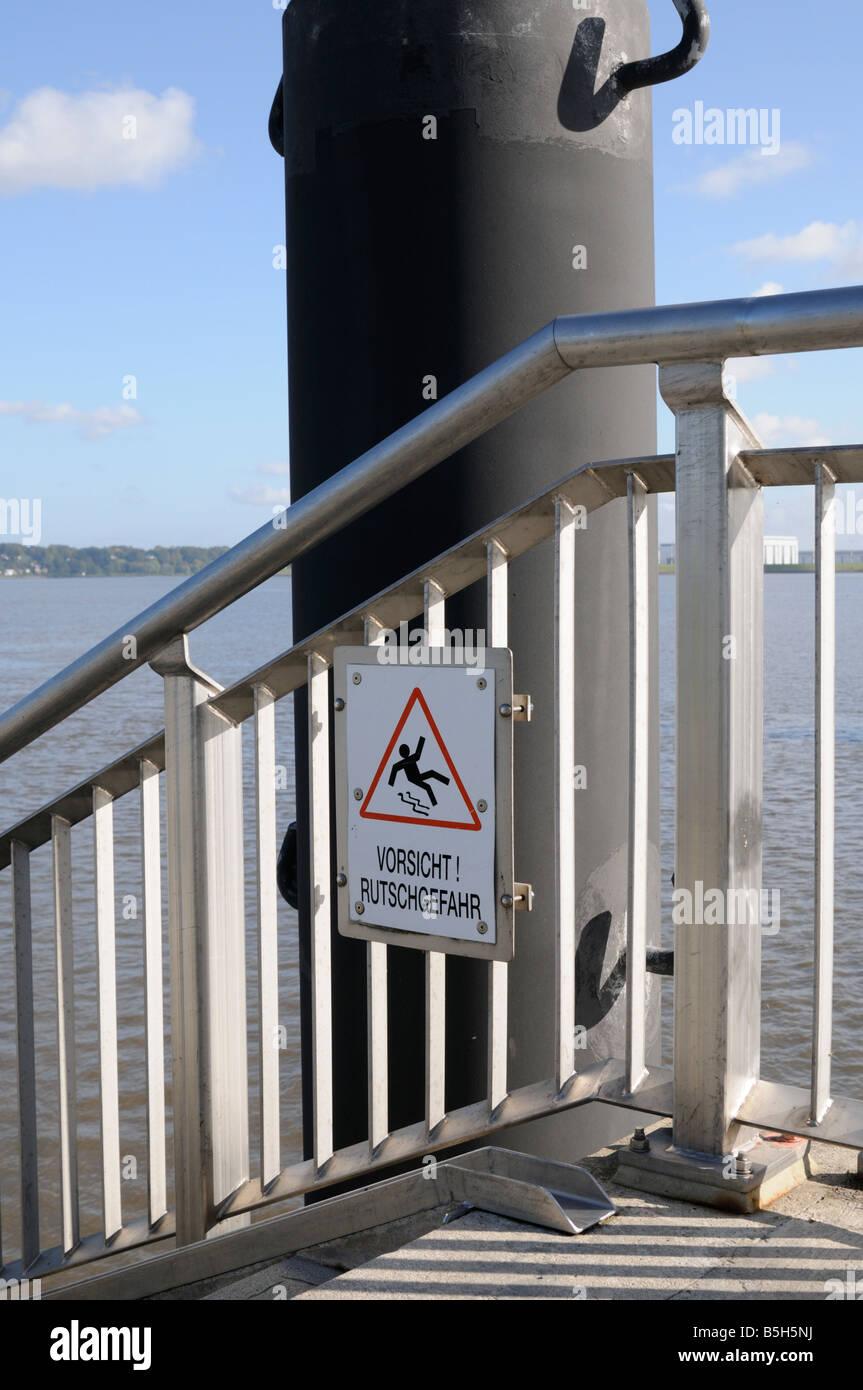Schild Vorsicht Rutschgefahr im Hamburger Hafen Deutschland Sign caution slip hazard in the Port of Hamburg Germany Stock Photo