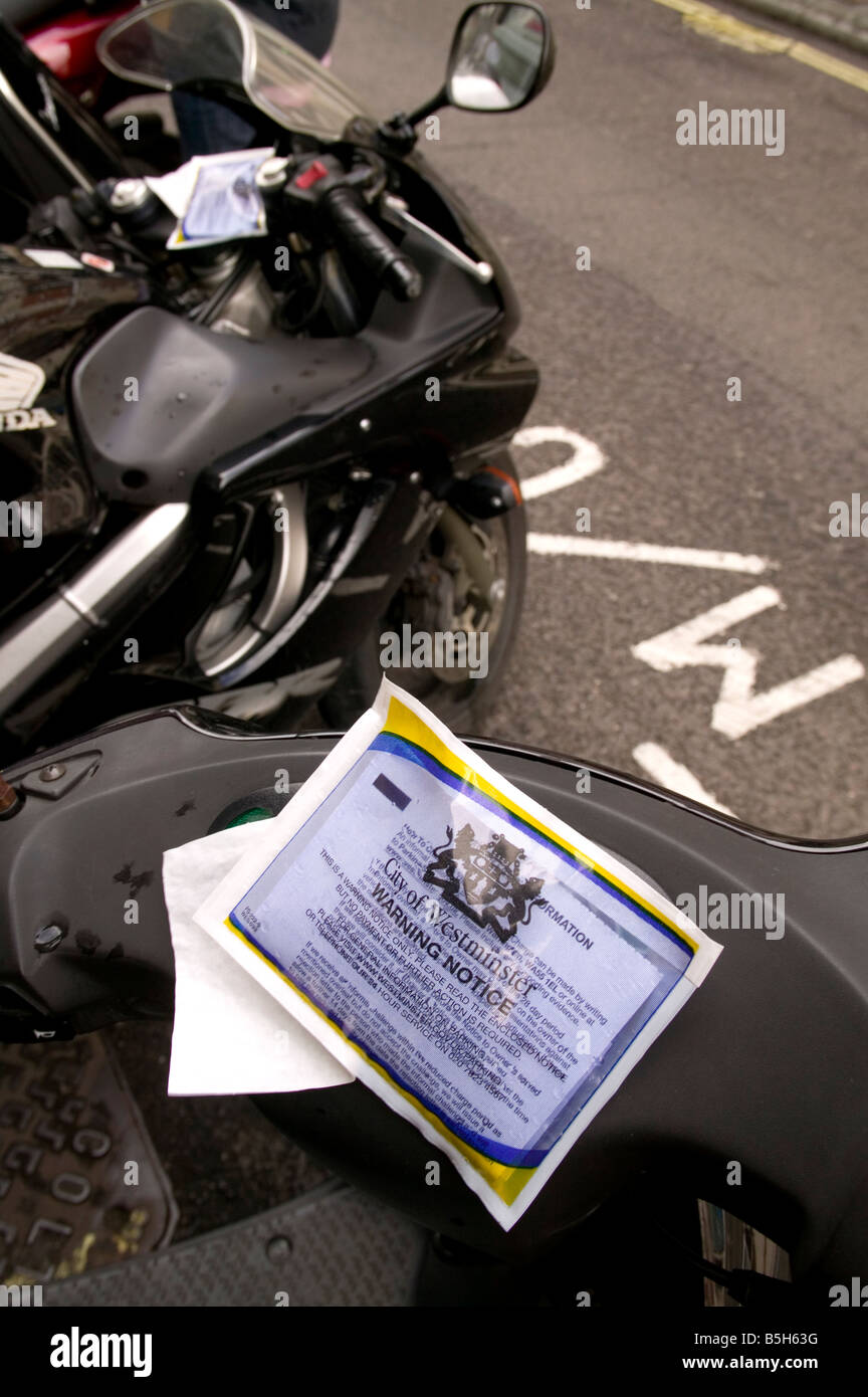 Warning notice given to motorcycle parked in Westminster that has introduced charges - Stock Image