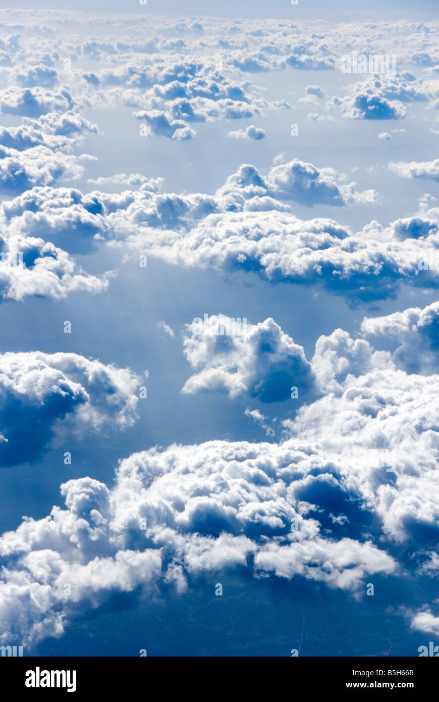 View above fluffy clouds at high altitude - Stock Image