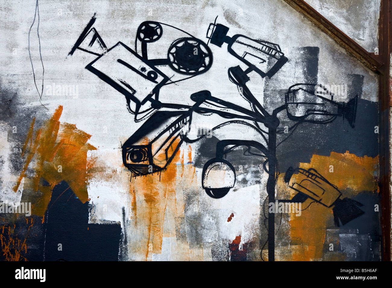 Graffiti in a brownfield site factory. Grafitti image on wall showing CCTV cameras Stock Photo