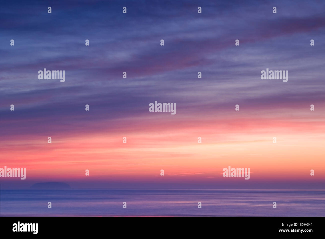 A pastel coloured sunset taken at Sandpoint near Weston Super Mare with Steepholm Island just visible in the background - Stock Image