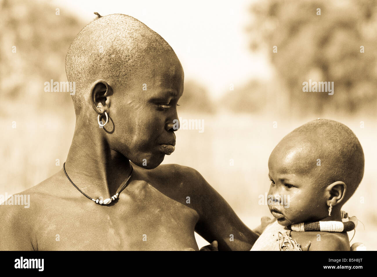A Dinka woman in Kotobi, South Sudan holds her child in her arms. - Stock Image