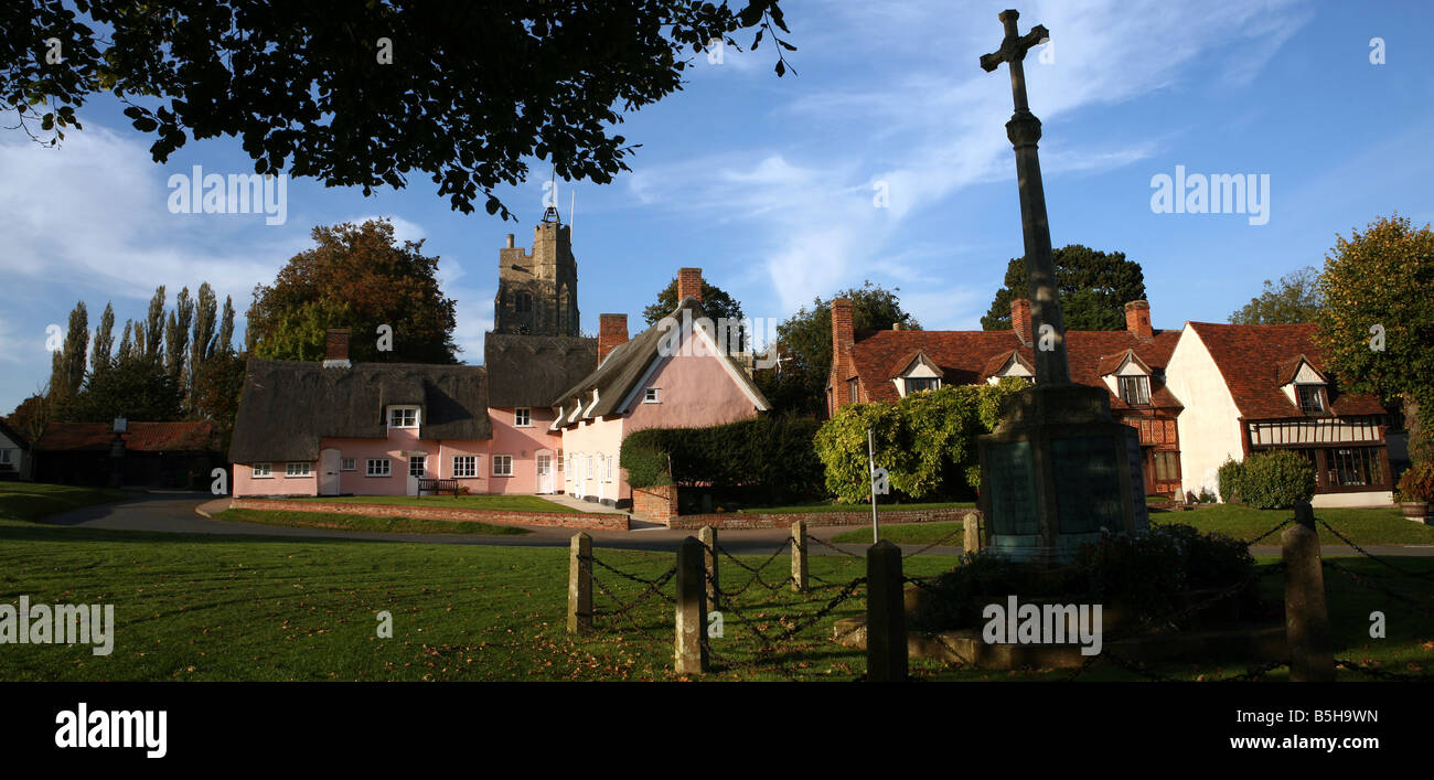 The village green of Cavendish in Suffolk showing pink thatched cottages and St. Mary's church and war memorial - Stock Image