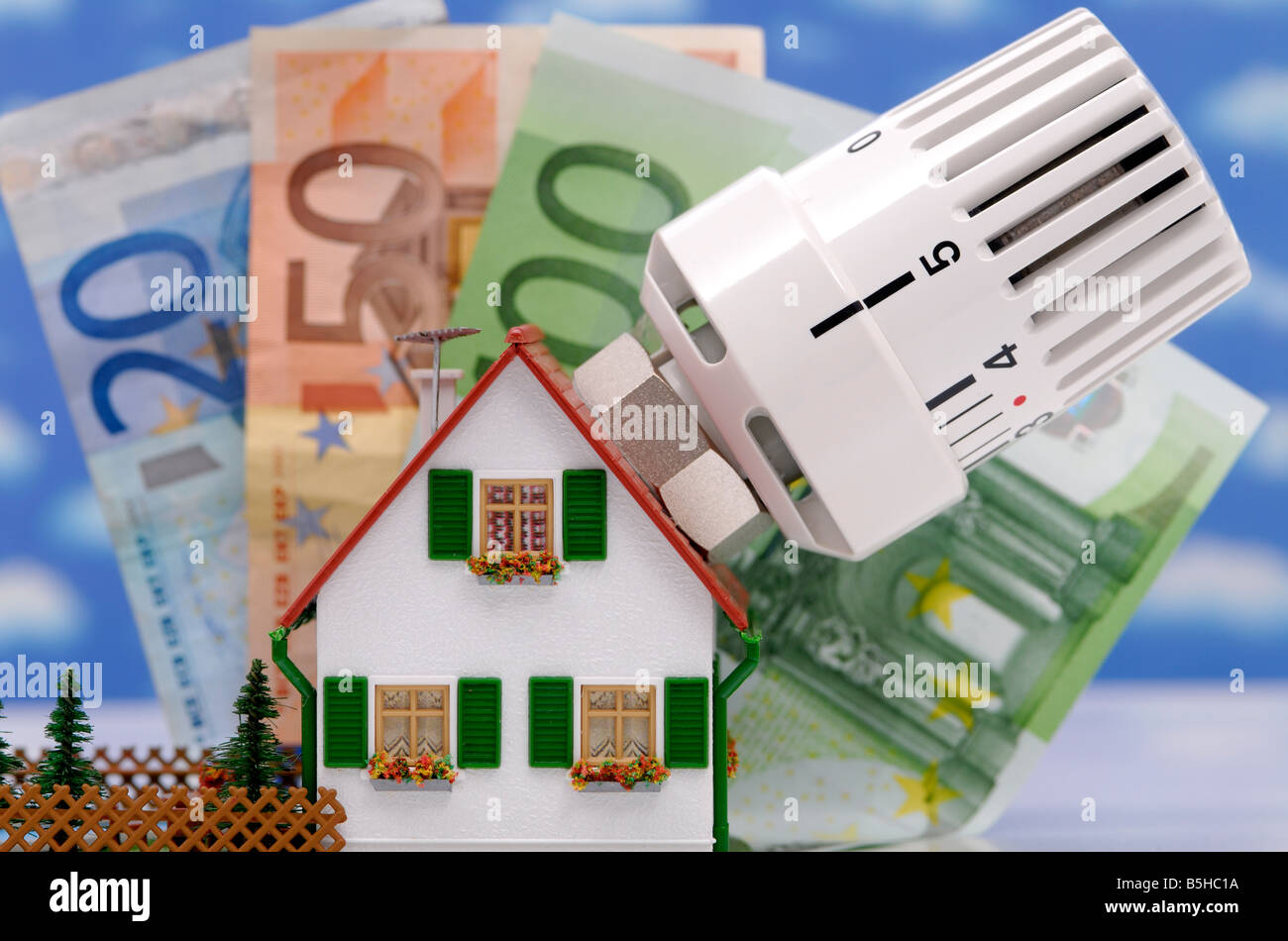 bank notes, a house and a heating, symbol for heating costs - Stock Image