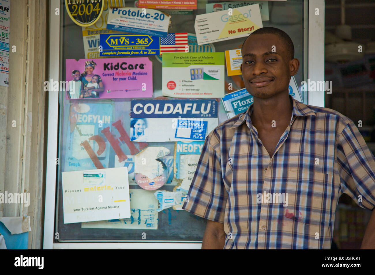 A Proprietary Patent Medicine Vendor (PPMV) stands in front of his shop in the Garki area of Abuja, Nigeria. - Stock Image