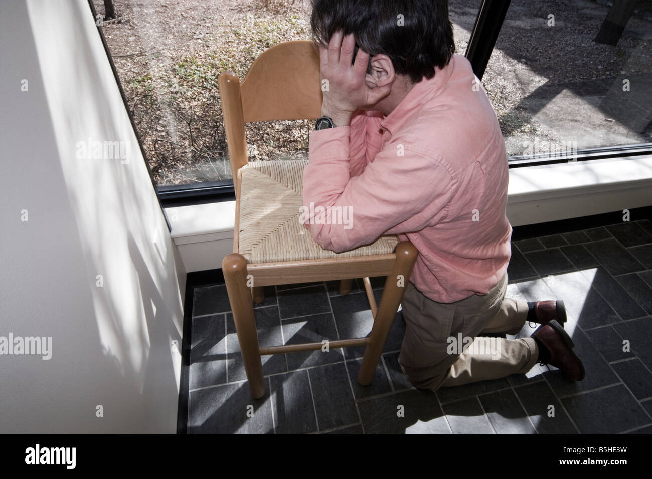 Man on his knees leaning against a chair MODEL RELEASED - Stock Image