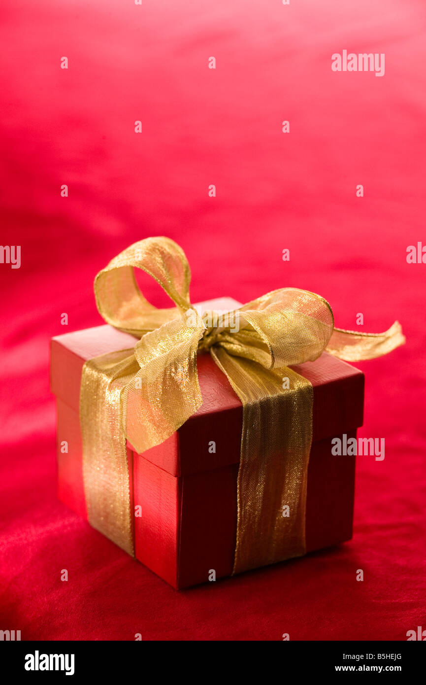 red gift box with a metallic gold ribbon - Stock Image