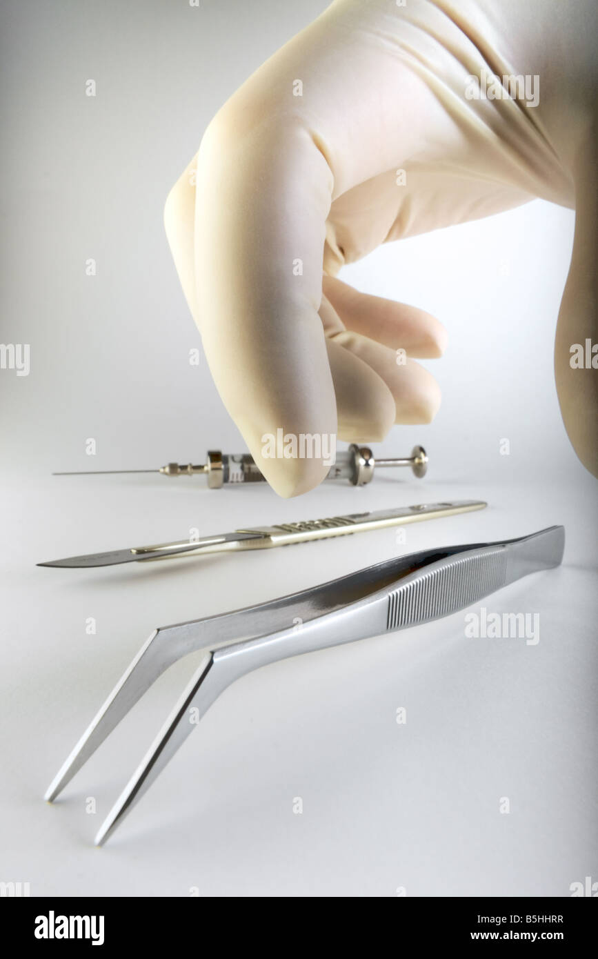 Hand picking up tweezers - Stock Image
