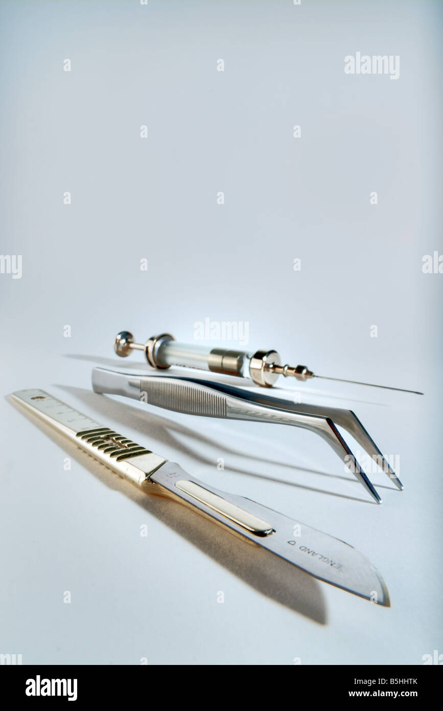 Scalpel, tweezers and a syringe - Stock Image