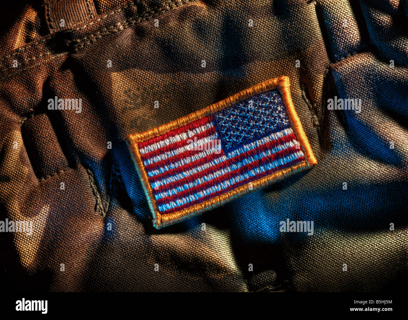 Detachable US flag patch on military camouflage fabric. Mirrored flag is for right shoulder. - Stock Image
