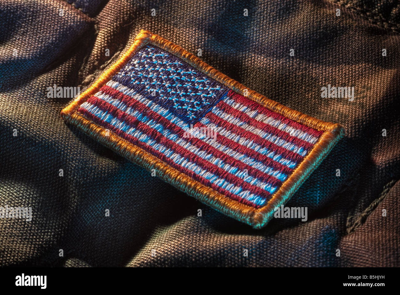 Detachable US flag patch on military camouflage fabric - Stock Image