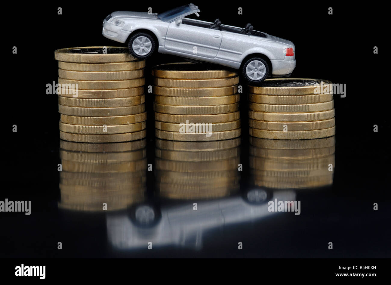 toy car upon some coins, taxes - Stock Image
