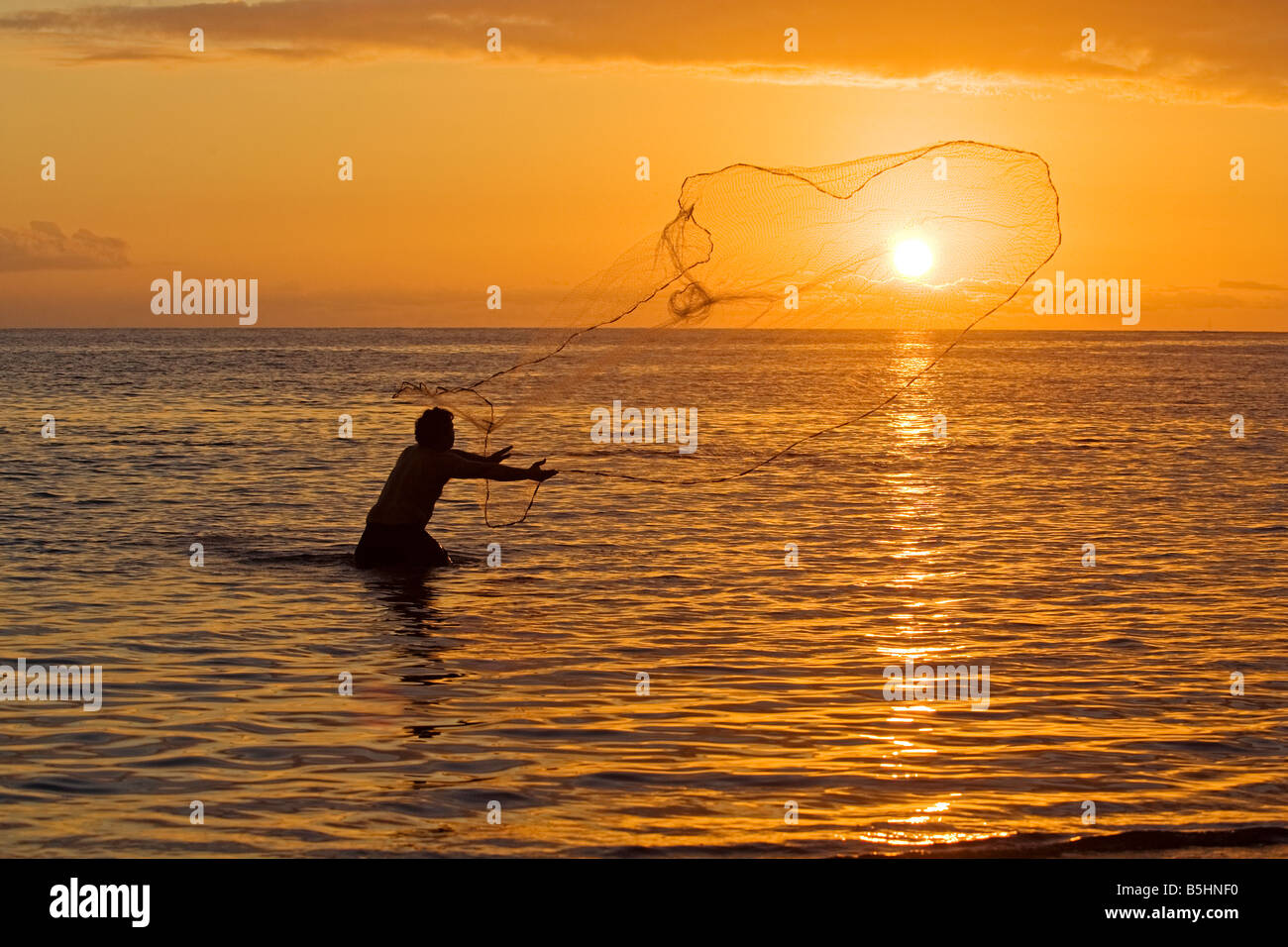 A Hawaiian man throws his net at sunset at Olowalu, Maui, Hawaii - Stock Image