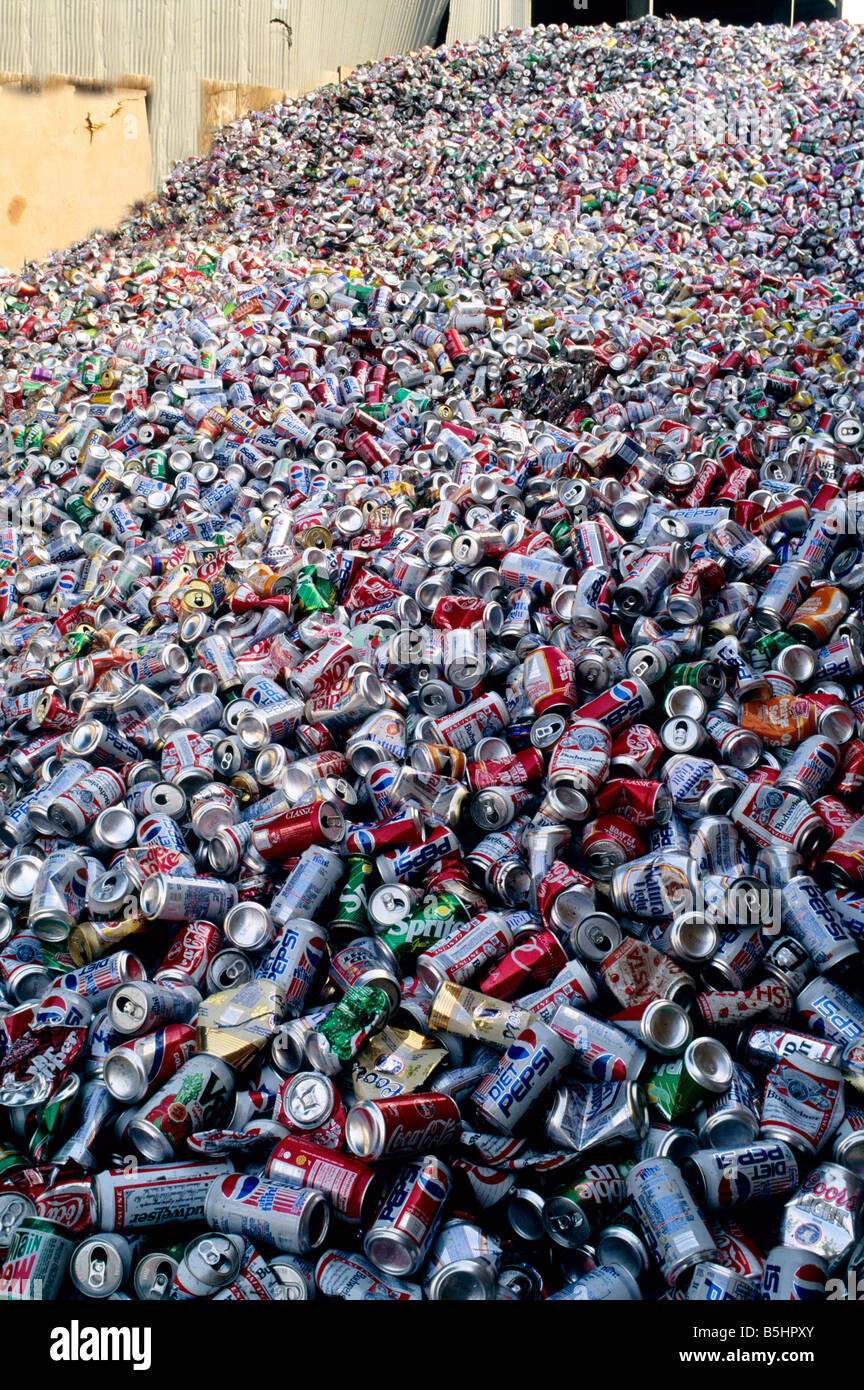 Piled aluminum soft drink cans at recycle center. - Stock Image