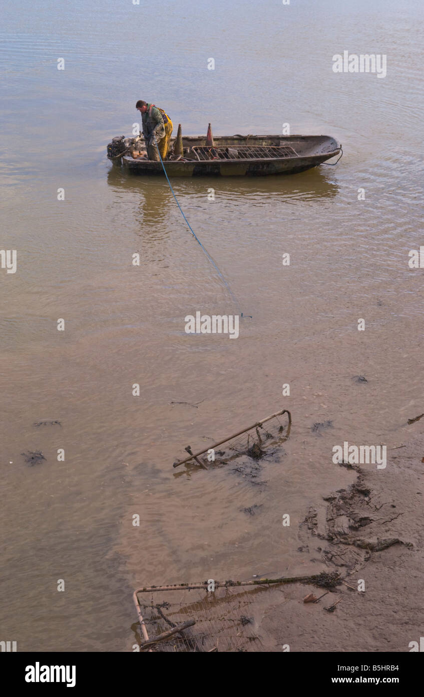 Two workmen using a small dingy remove rubbish from the mud of the tidal River Usk in Newport town centre South - Stock Image