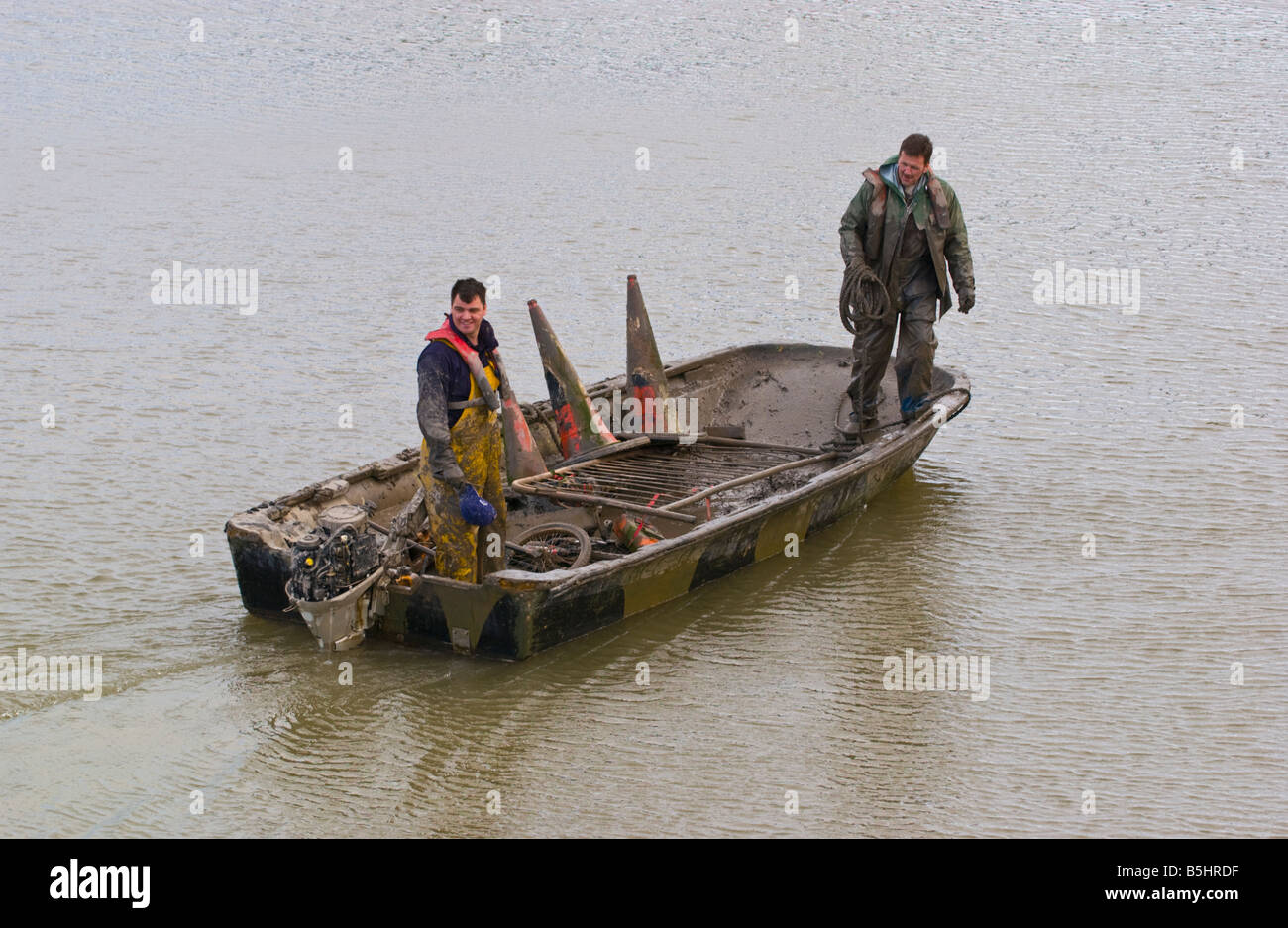 Two workmen using a small dingy remove rubbish from the mud of the tidal River Usk in Newport City centre South - Stock Image