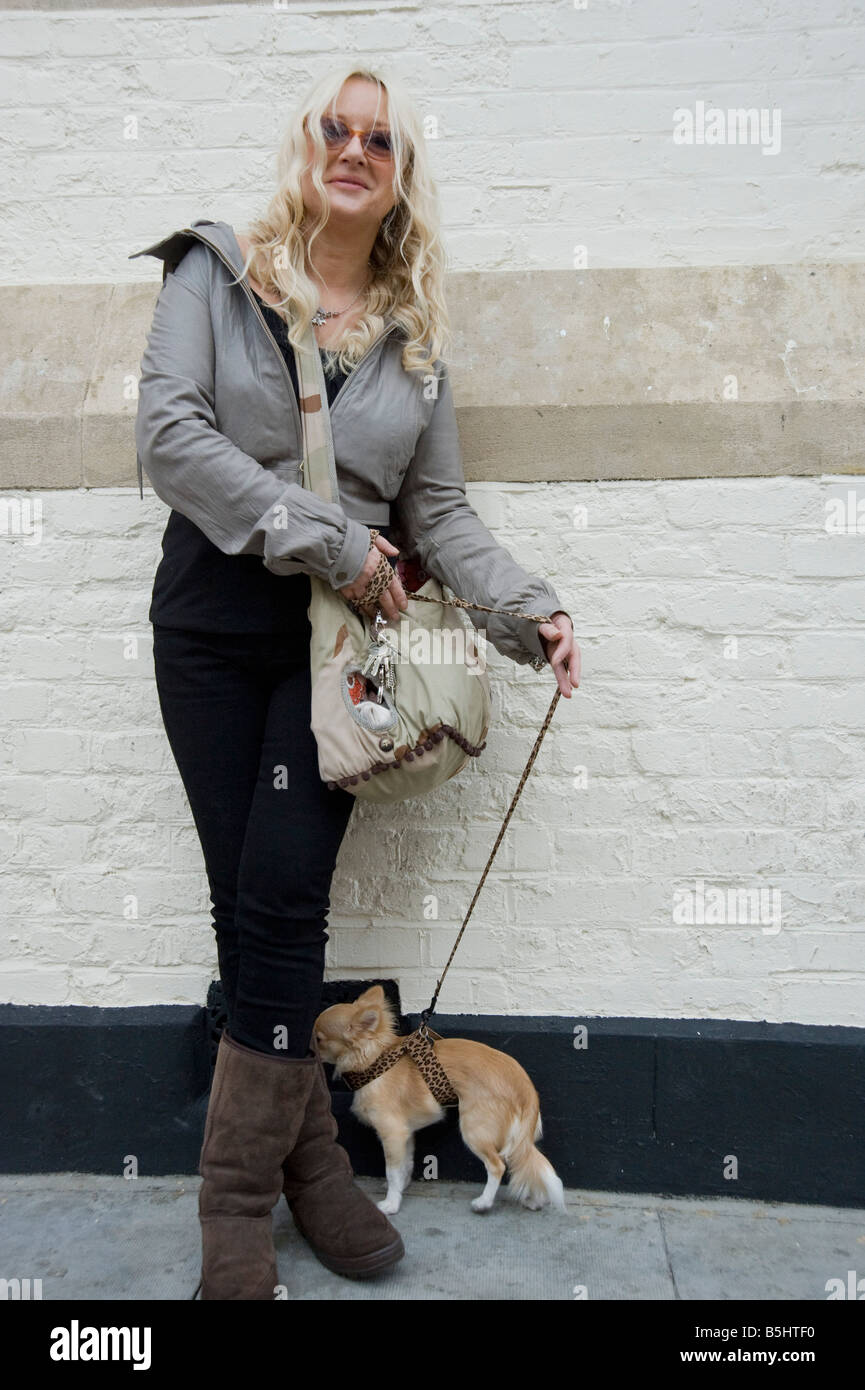 A woman wearing Ugg boo leans against a wall with her small pedigree dog on Kensington Park Road in Nottinghill - Stock Image