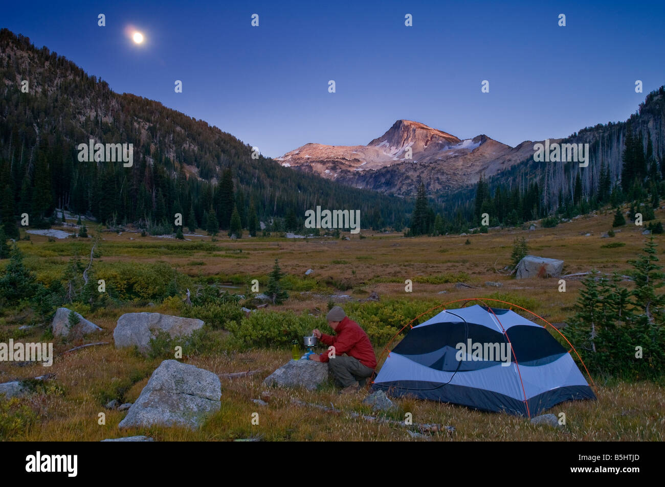 Backpacking camper Lostine River valley meadow moon rise over Eagle Cap mountain Eagle Cap Wilderness Wallowa Mountains - Stock Image