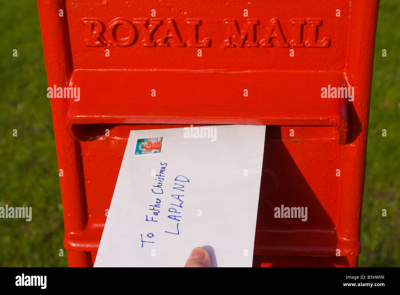 A letter being posted in Uk Royal Mail postbox addressed to Father Christmas  Lapland telling of child's Christmas - Stock Image