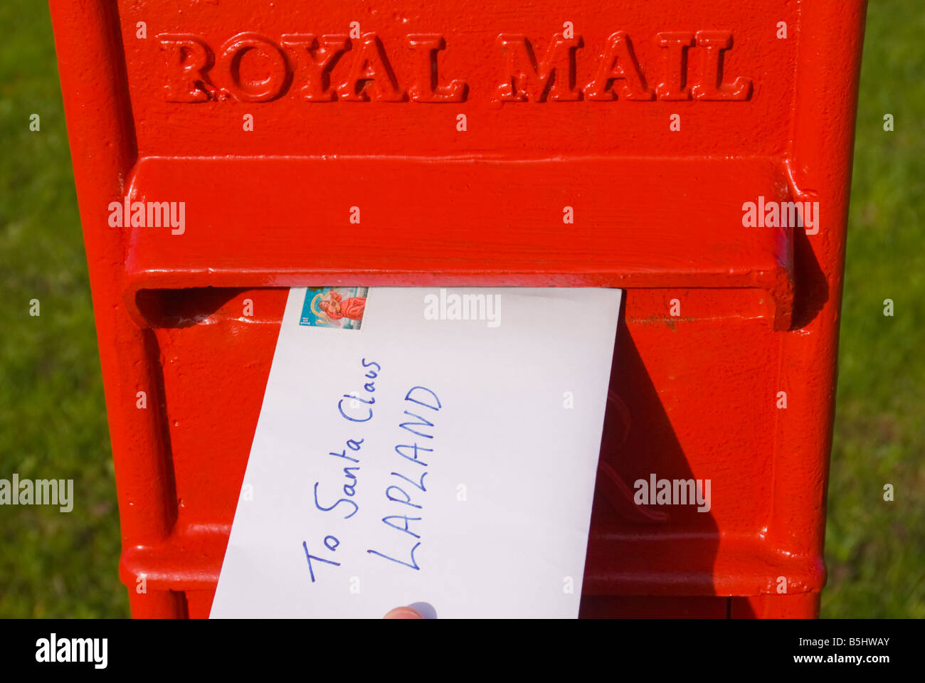 A letter being posted in Uk Royal Mail postbox addressed to Santa Claus Lapland telling of child's Christmas - Stock Image