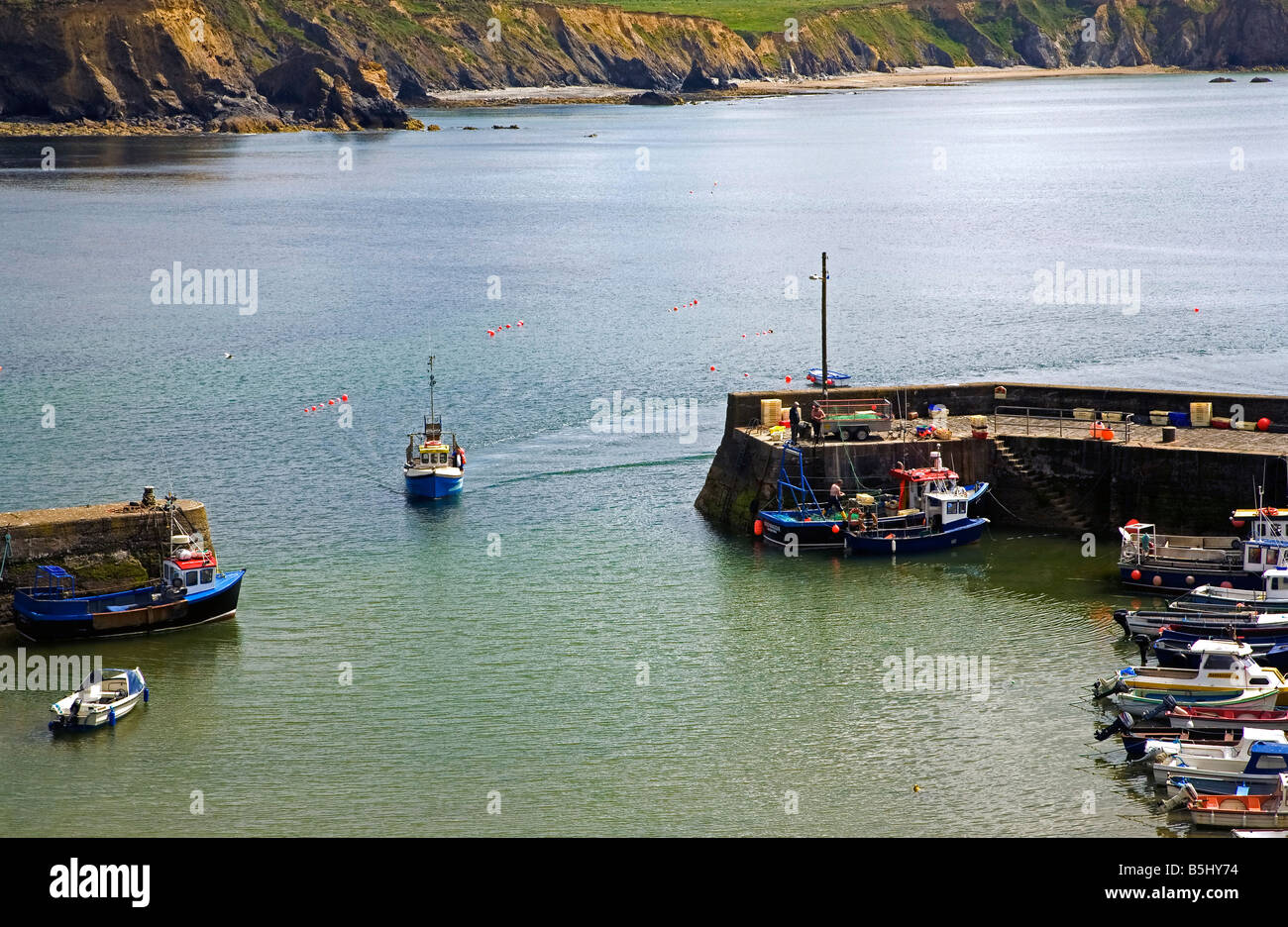In shore Fishing Boat Entering Boatstrand Harbour, Copper Coast, County Waterford, Ireland - Stock Image