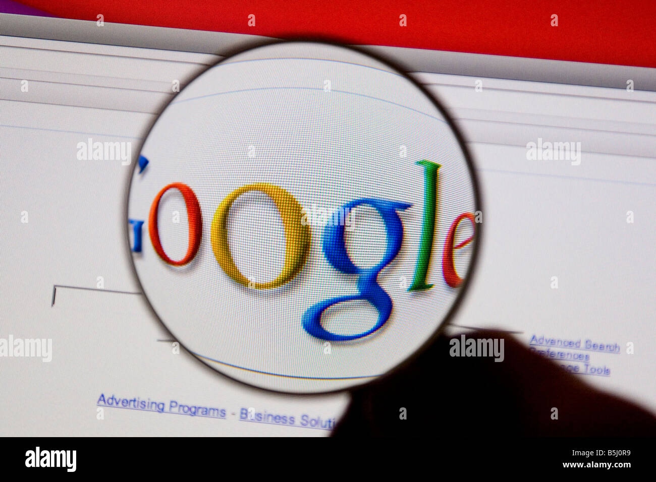 Google logo on a computer screen with a magnifying glass. - Stock Image