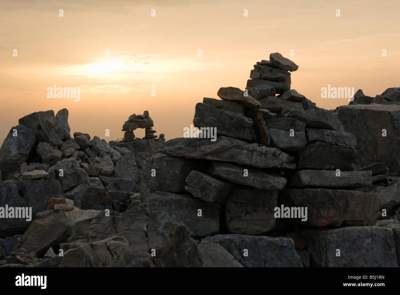piles of stones rocks put together by visitors into structures, bridges, sculptures on the Croatian island of Zut - Stock Image