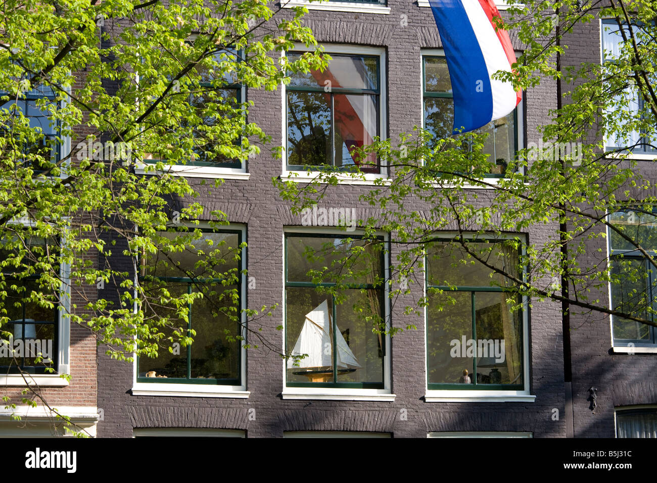 Amsterdam. House on a canal in the Jordaan with Dutch national flag and a model sailing-boat on the windowsill. - Stock Image