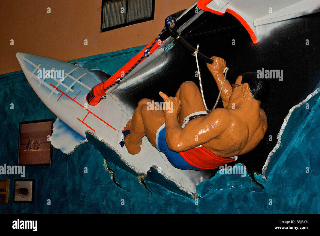 Three dimensional mixed media windsurfer on surfboard wave jumping sculpture art in bar - Stock Image