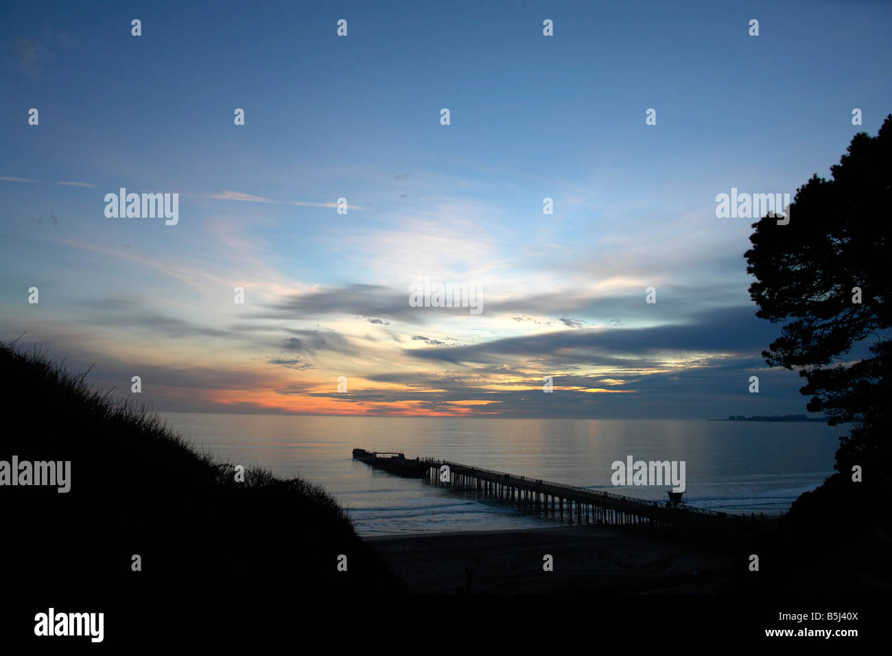Sunset over Seacliff beach in Aptos, CA. The Palo Alto Cement ship can be seen at the end of the pier in the background. - Stock Image
