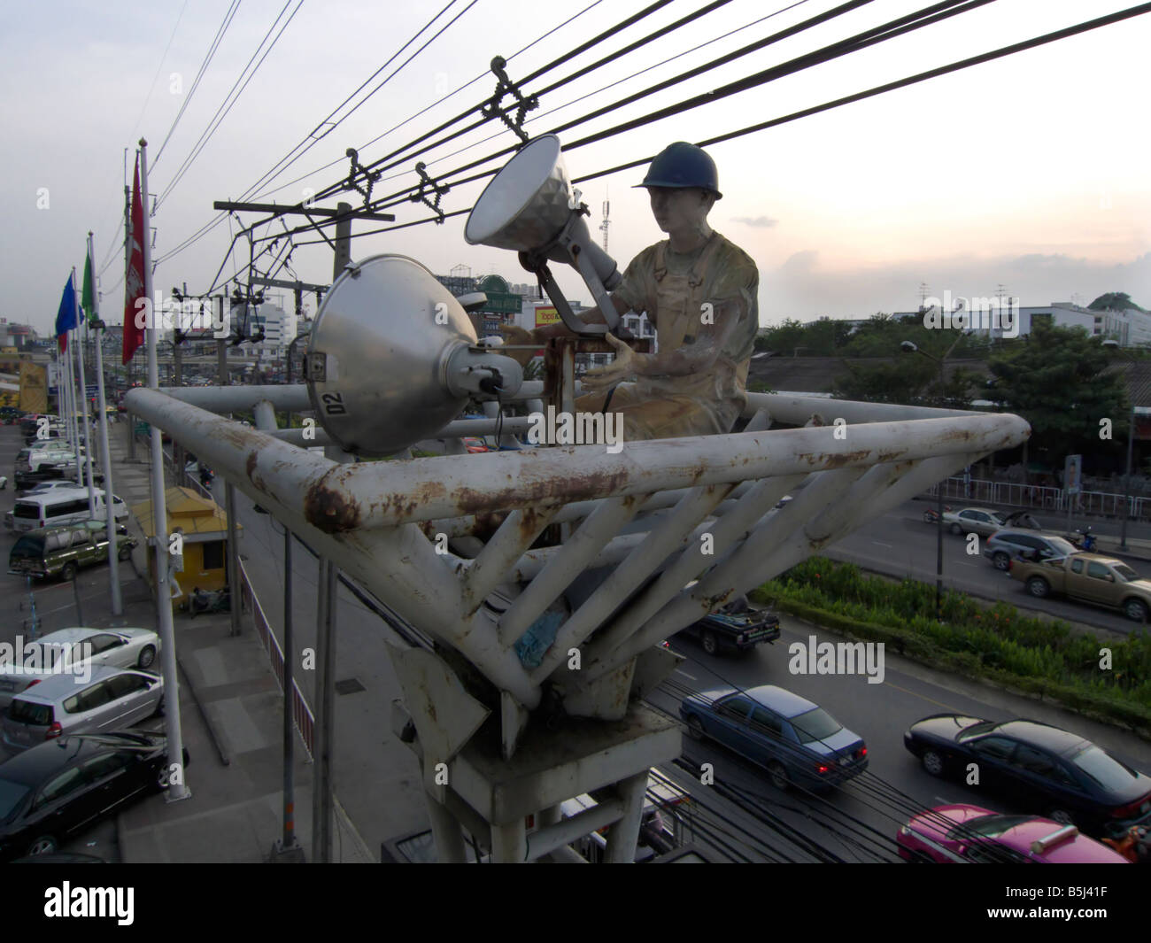 A statue of a worker sits atop a lighting tower while the statue of a girl climbs a flagpole in the background. - Stock Image