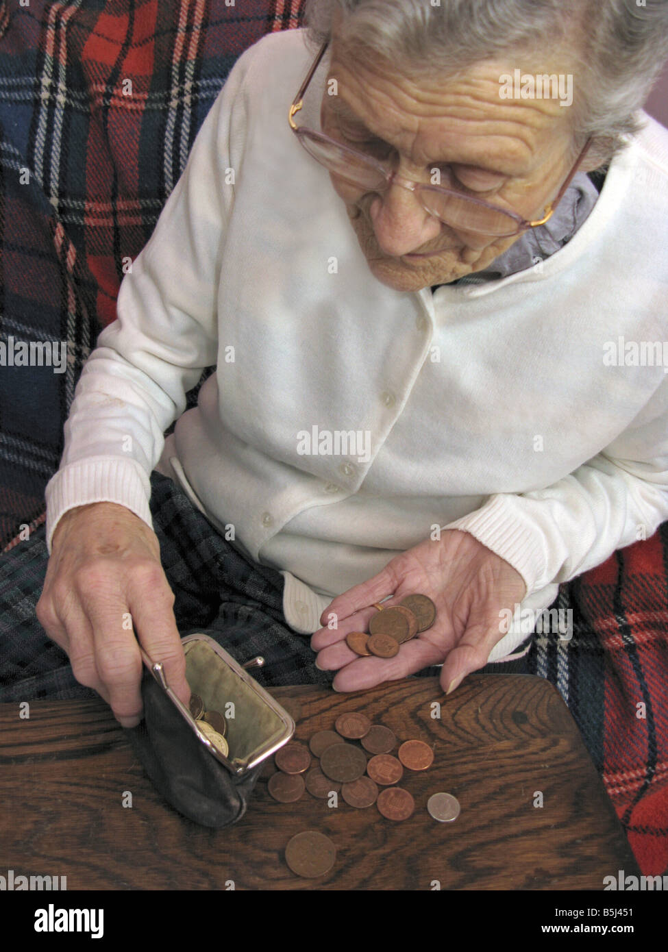 elderly woman counting the pennys in these troubling times - Stock Image