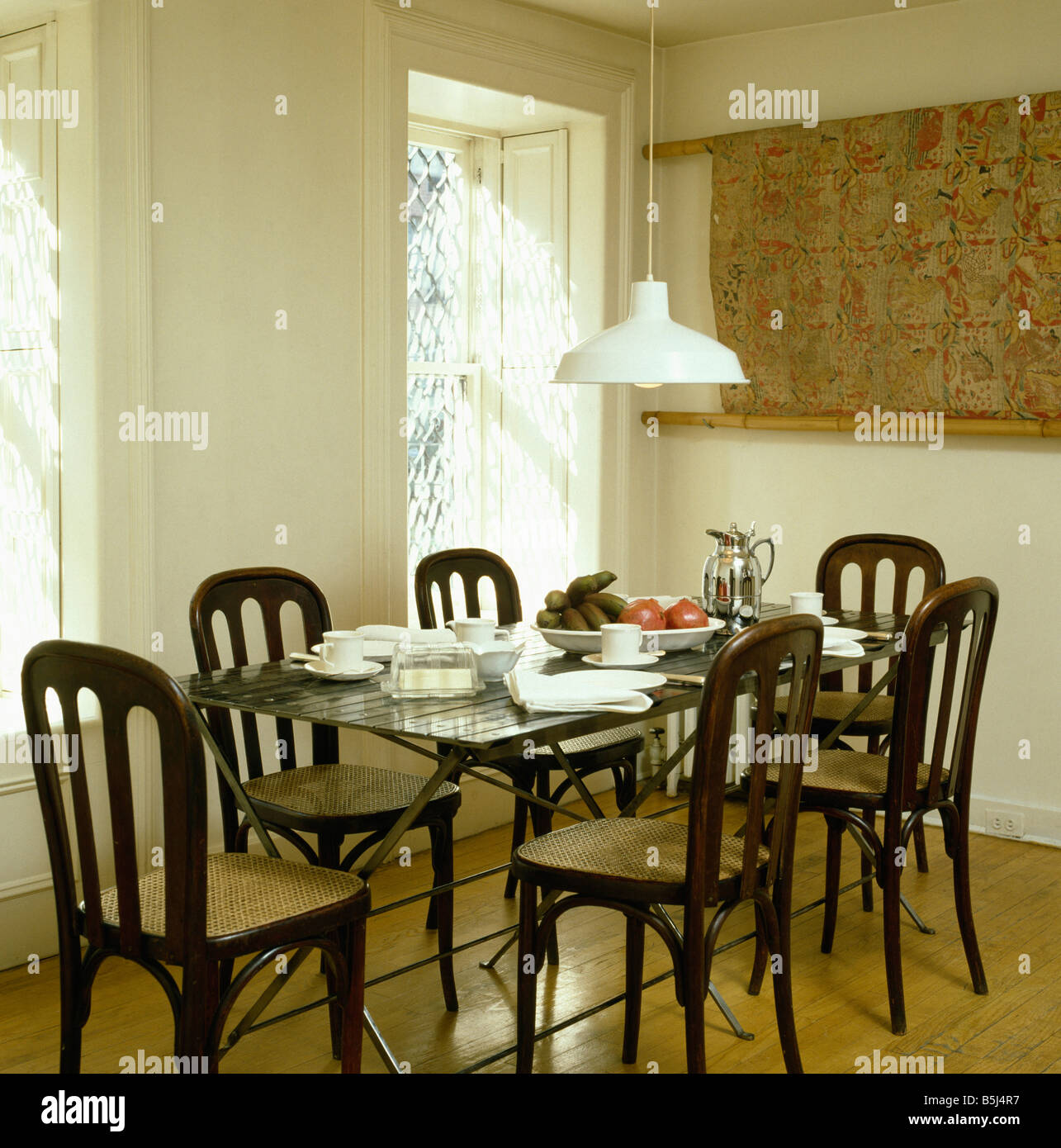 White Pendant Light Above Table Set With White China In Modern Dining Room  With Antique Dining Chairs And Wooden Floor