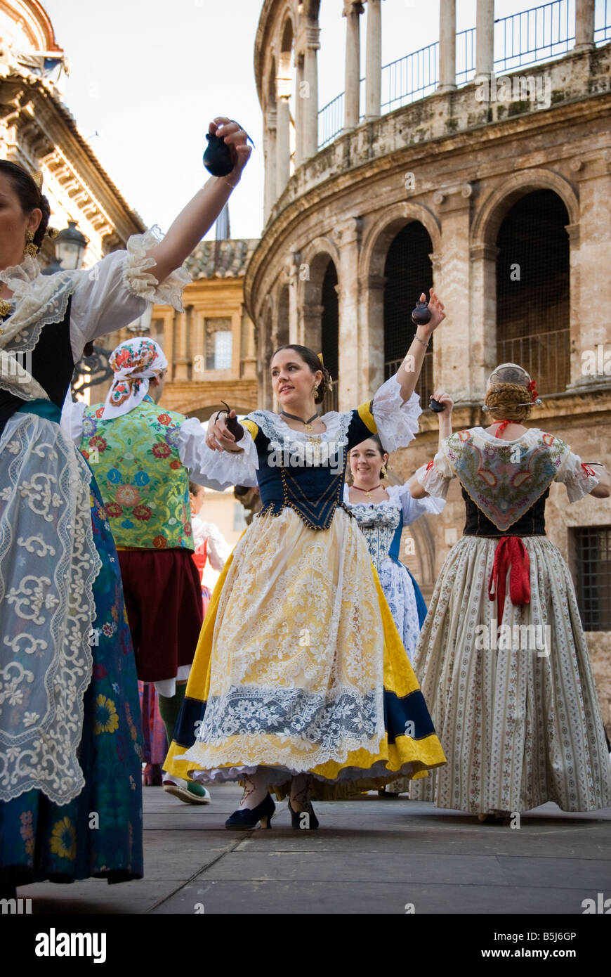 Traditionally dressed Spanish woman dancing on Plaza de la Virgen in the historical city centre of Valencia Spain - Stock Image