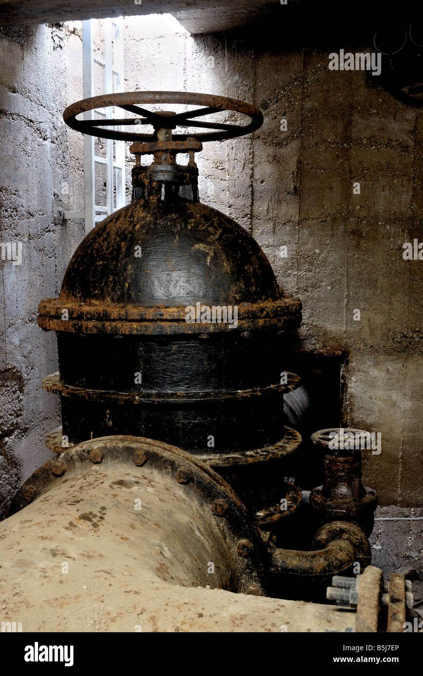 Water valve in the fresh water supply system of city Ljubljana. Underground shot with daylight at the back. - Stock Image