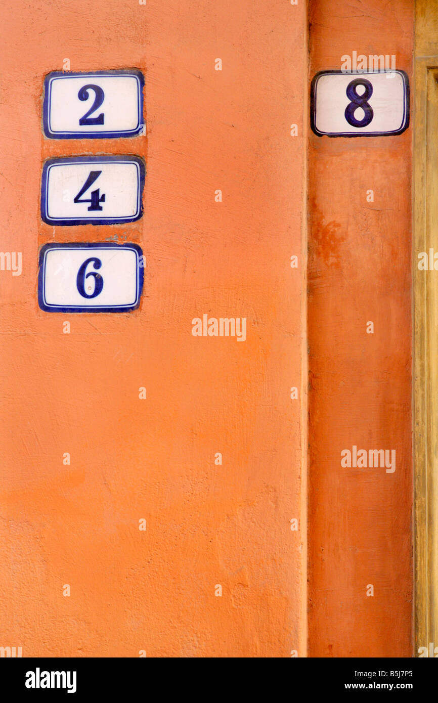 House numbers on orange wall, Bologna, Italy. Stock Photo