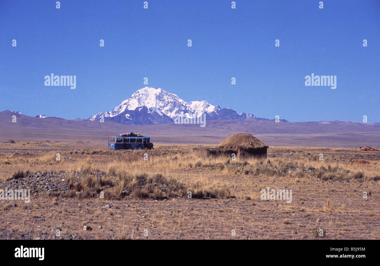Local bus driving across the altiplano near a rustic hut, Mt Huayna Potosi in background, Bolivia - Stock Image