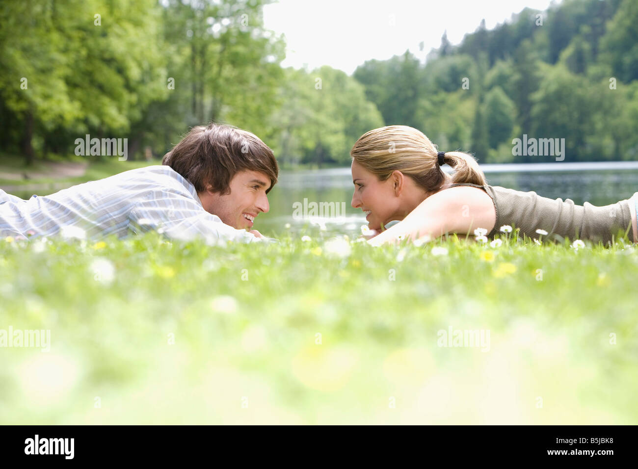 young couple lying in grass tenderly looking at each other - Stock Image