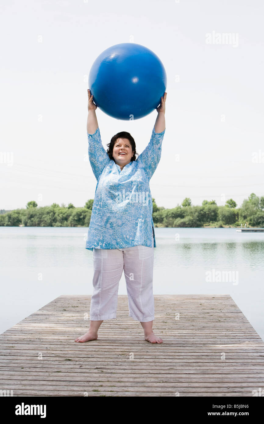 overweight woman doing exercises with blue ball on pier by lake - Stock Image