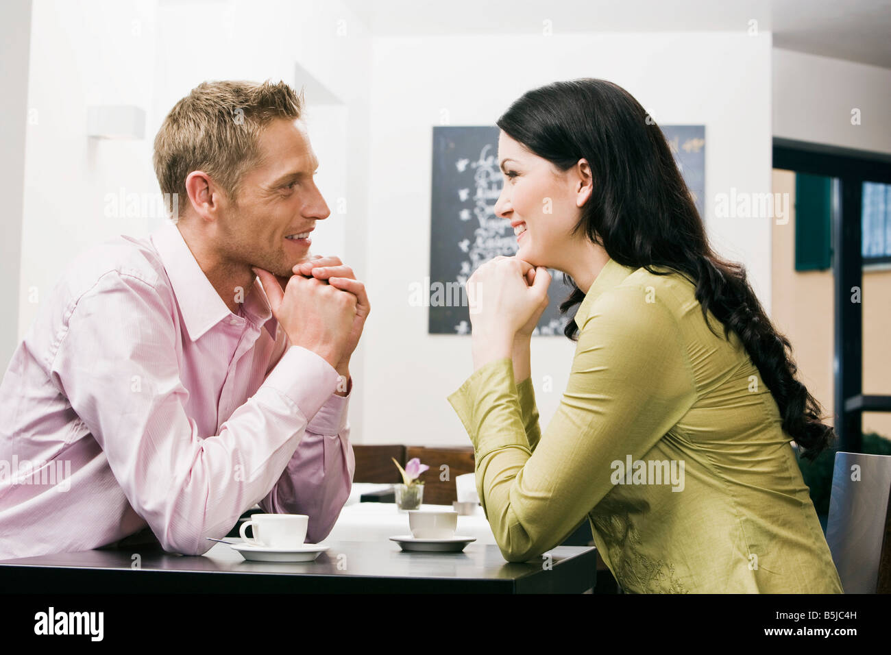 young couple at cafe flirting with each other - Stock Image