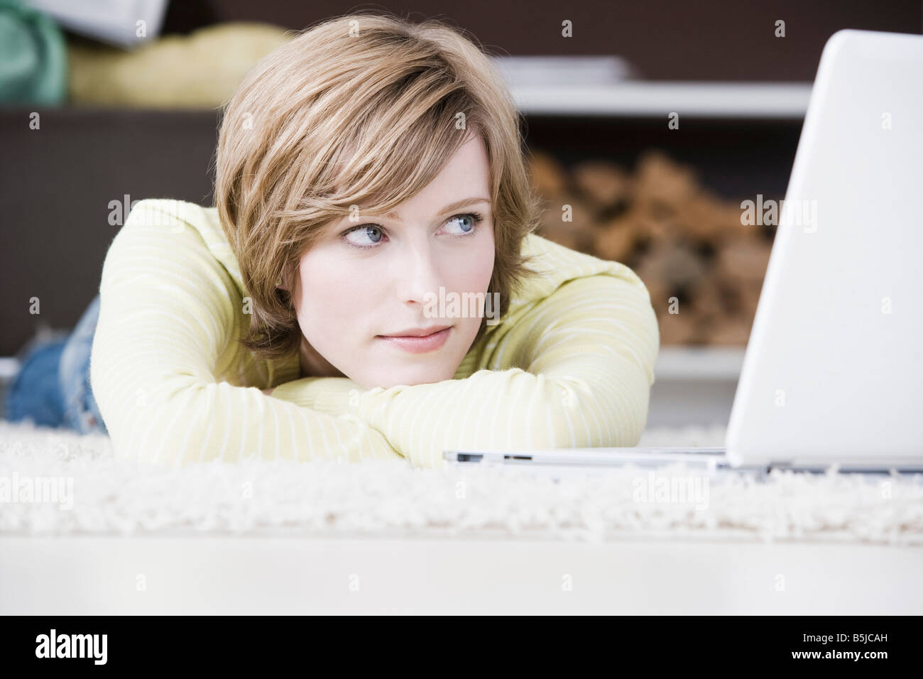 portrait of young woman lying on floor at home in front of laptop computer - Stock Image