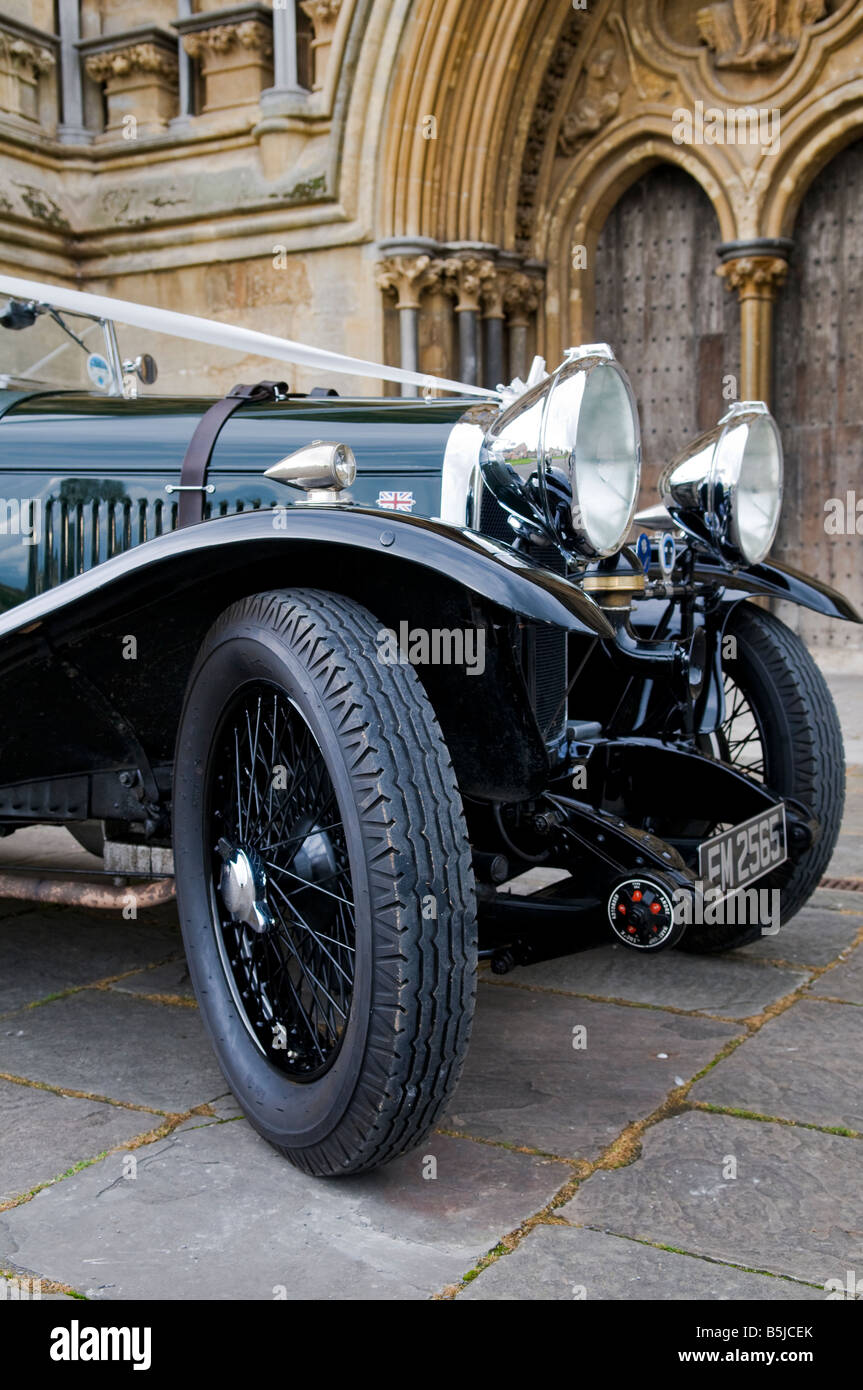A renovated 1930's bottle green, Lagonda classic car with white ribbons waiting outside Wells Cathedral at a - Stock Image