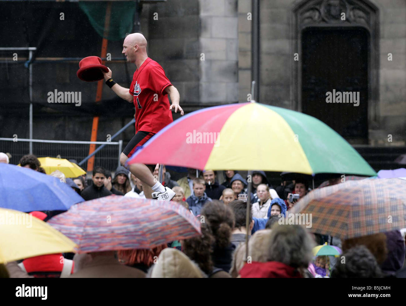 Street performers at the Edinburgh Fringe Festival The Royal Mile, A unicyclist performing in the rain - Stock Image