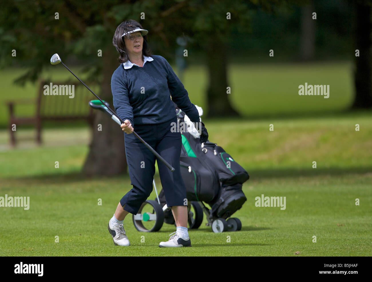 Lady playing a shot off the fairway - Stock Image