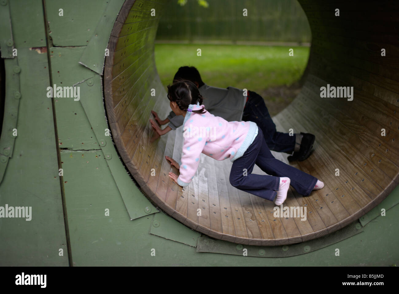 Five year old girl in playground with her brother - Stock Image