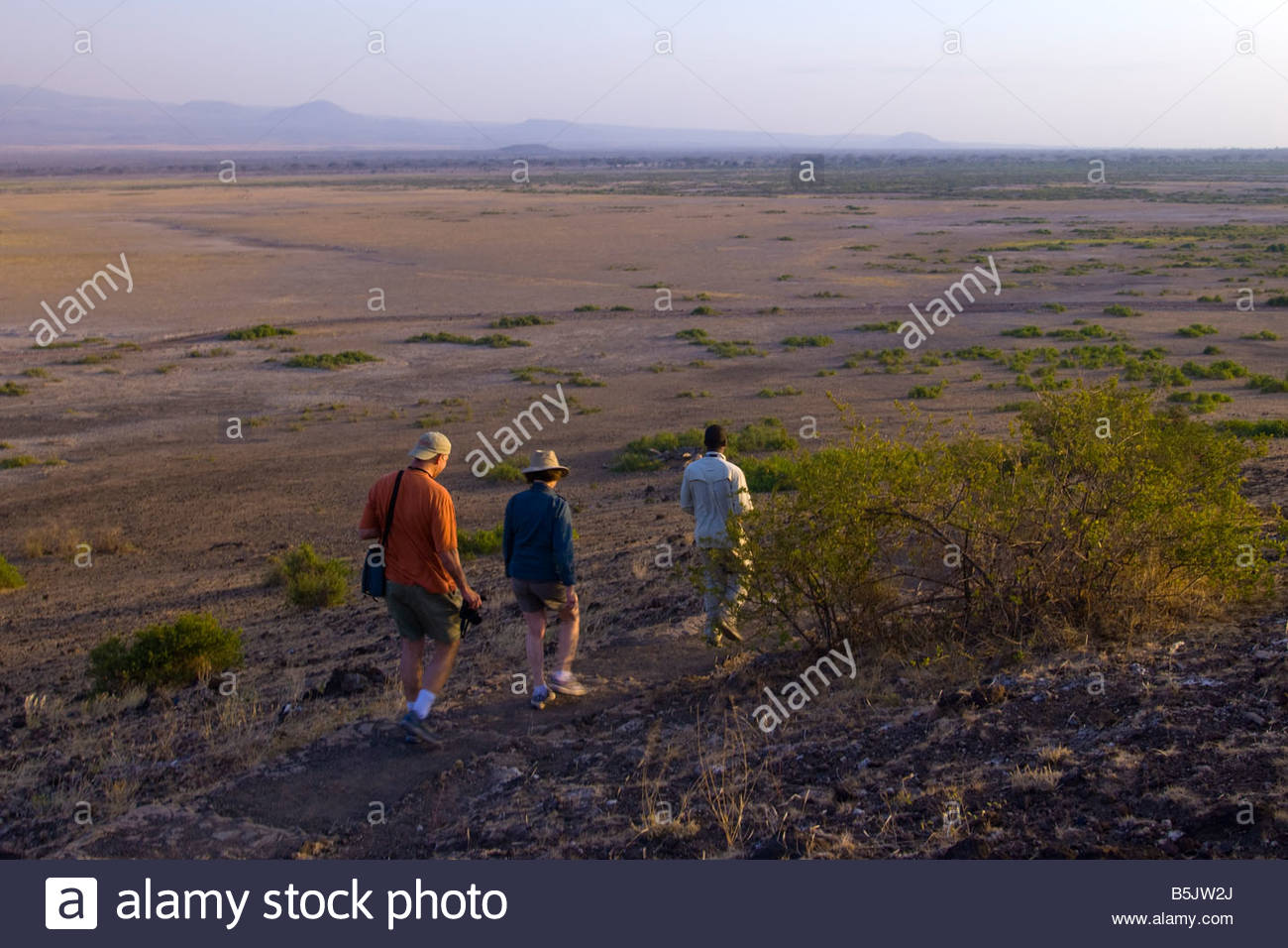 Tourists on a short hike down from Observation Hill Noomotio with Mount Kilimanjaro in background Amboseli National - Stock Image