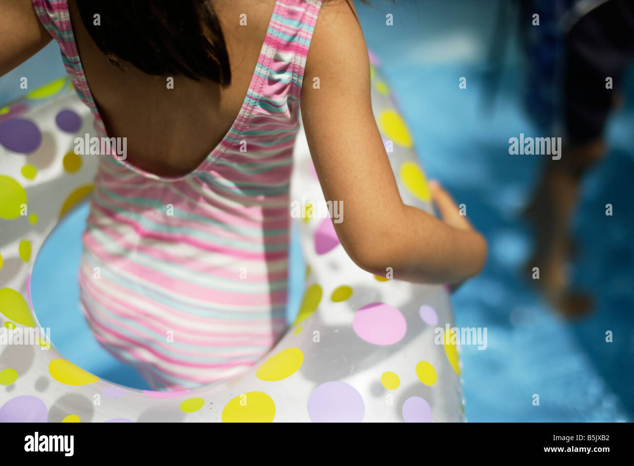 Five year old girl in paddling pool with inflatable rubber ring - Stock Image